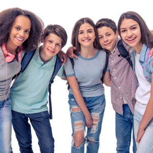 Group of teenage boys and girls with school backpacks is looking at camera and smiling isolated on white